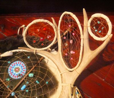 detail of turkey feathers and crow beads on dreamcatcher shield
