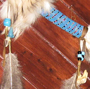 detail of beadwork and buffalo tooth and coyote tooth on spirit chaser stick