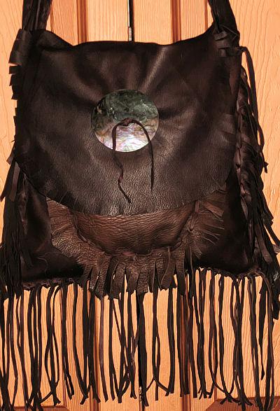 detail of abalone shell on buckskin bag
