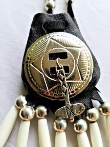 detail of concho and tomahawk charm on medicine bag