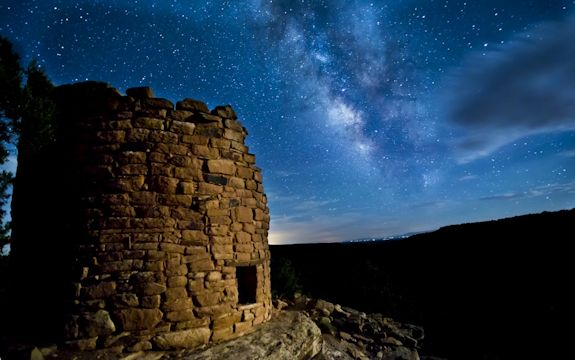 A small, round brick building stands on a flat plain with a starry sky above it.