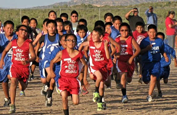Boys in red and blue athletic clothes run across a dirt field.