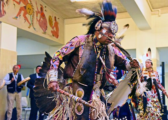 A Native American man wearing traditional clothes and feathers dances inside a large room.