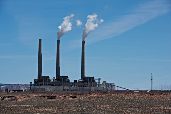 Three large smokestacks rise above a large power plant on a desert plain.